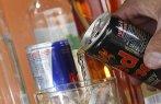 Imagem de embalagens de bebidas energérticas em copo com bebida alcoólica.